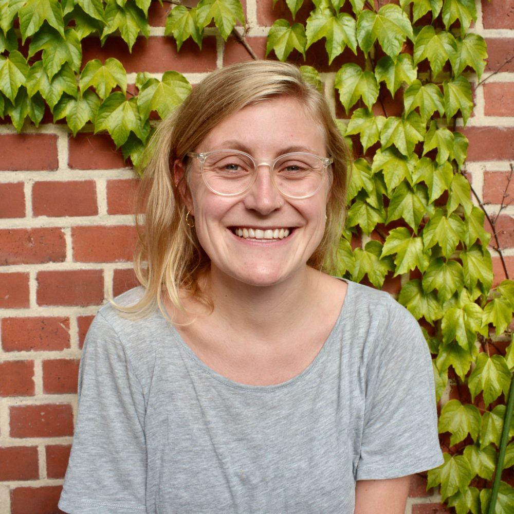 Das Bild zeigt die Geschäftsführung Lena. Sie steht vor einer mit Efeu bewachsenen Backsteinwand und lacht in die Kamera. © Servicestelle Jugendbeteiligung e.V., 2020