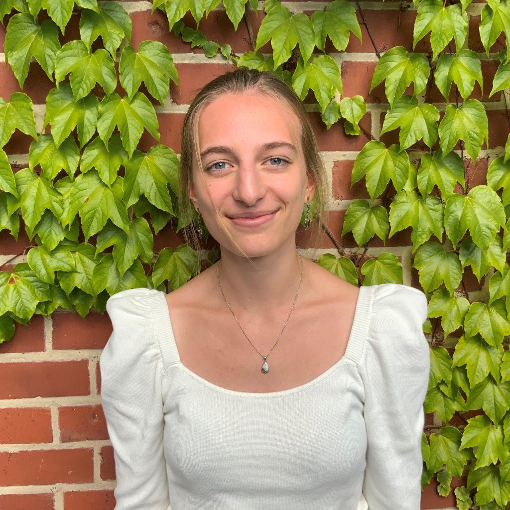 Das Bild zeigt die Freiwilligendienstleistende Charlotte. Sie steht vor einer mit Efeu bewachsenen Backsteinwand und lacht in die Kamera. © Servicestelle Jugendbeteiligung e.V., 2020
