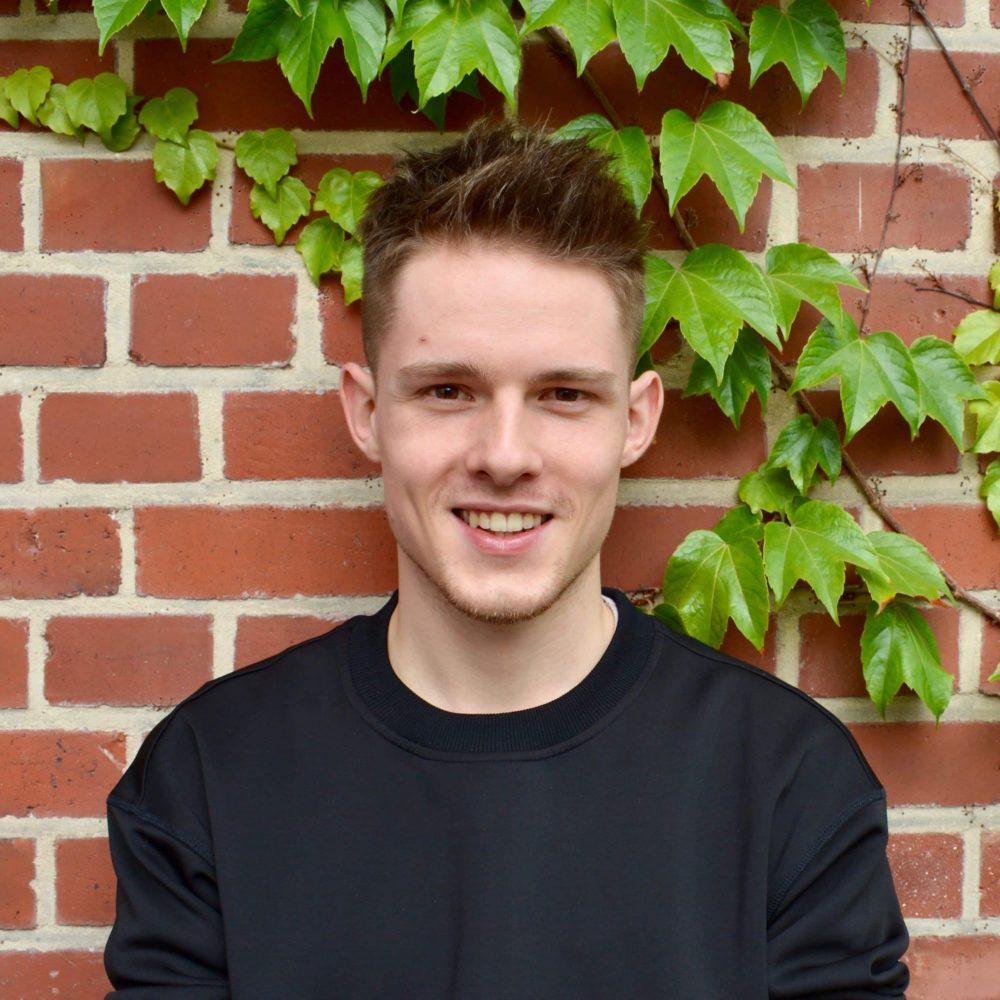 Das Bild zeigt Louis von der Servicestelle Jugendbeteiligung. Er steht vor einer mit Efeu bewachsenen Backsteinwand und lacht in die Kamera. © Servicestelle Jugendbeteiligung e.V., 2020