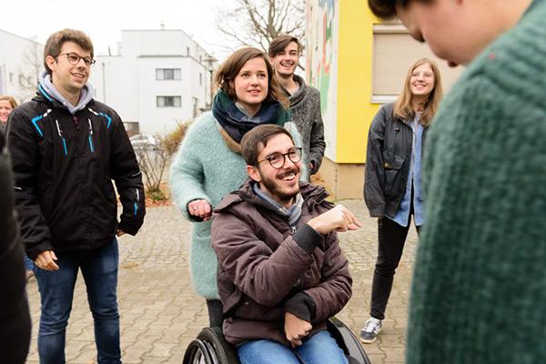 Im Fokus ist ein junger Mann im Rollstuhl zu sehen. Er wird von einer jungen Frau geschoben. Im Hintergrund sind weitere junge Menschen zu erkennen. © Servicestelle Jugendbeteiligung e.V., 2016