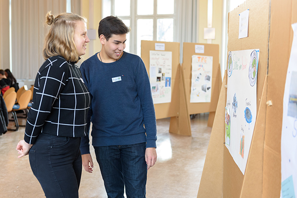 Auf dem Bild sieht man zwei Personen, die sich Plakate anschauen, die auf Pinnwänden aus Pappe angebracht sind. Im Hintergrund sieht man mehr Pinnwände. © Servicestelle Jugendbeteiligung e.V., 2020