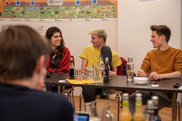 Auf dem Bild sieht man drei Personen, die an Konferenztischen nebeneinander sitzen und sich lächelnd anschauen © Servicestelle Jugendbeteiligung e. V., 2020