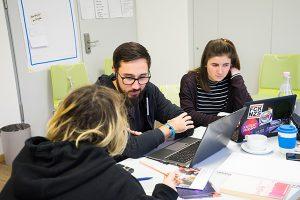 Das Bild zeigt drei Dein Ding Projektmacher*innen während ihrer Projektplanung. Sie sitzen mit Laptops am Tisch und diskutieren © Servicestelle Jugendbeteiligung e. V., 2020
