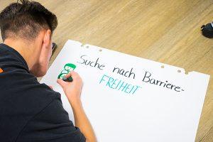 """Das Bild zeigt eine Person, die am Boden liegt und ein Flipchart mit der Überschrift """"Auf der Suche nach Barrierefreiheit"""" gestaltet.© Servicestelle Jugendbeteiligung e. V., 2020"""