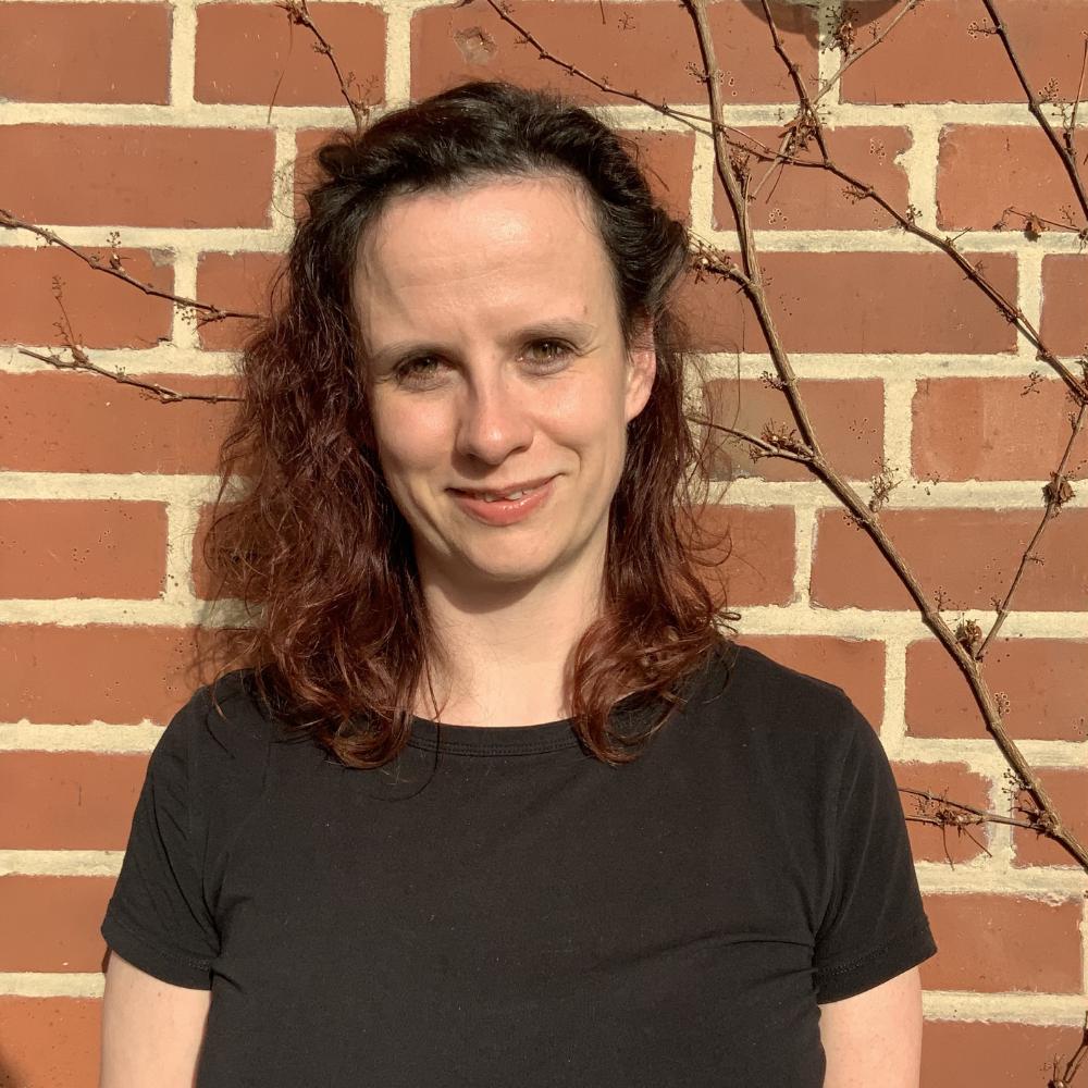 Das Bild zeigt Chrissy von der Servicestelle Jugendbeteiligung. Sie steht vor einer Backsteinwand und lacht in die Kamera. © Servicestelle Jugendbeteiligung e.V., 2021