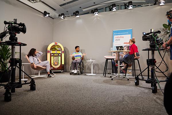 Das Bild zeigt die Moderatorinnen Ninia und Suri im Talk mit dem YouTuber Leeroy beim InkluDay 2020. Sie sitzen in einer Studiokulisse. © Anna Spindelndreier, 2020