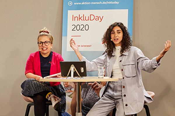 Auf dem Bild zu sehen sind Ninia und Suri, die beiden Moderatorinnen des InkluDay 2020. Sie sitzen an einem Tisch und lachen in die Kamera © Anna Spindelndreier, 2020