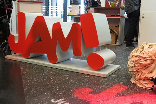"""Der Schriftzug """"JAM!"""" als großer roter Aufsteller steht auf dem Fußboden."""