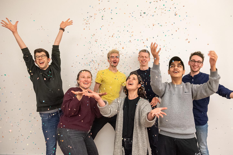 Das Bild zeigt sieben Personen, die lachend vor einer weißen Wand stehen und freudig Konfetti in die Luft werfen. © Servicestelle Jugendbeteiligung e. V., 2020