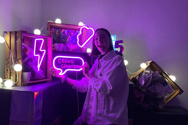 """Auf dem Bild sieht man unserer Mitarbeiterin Franzi, die vor einer bunten Kulisse mit pinken Neonfarben steht. Sie hält eine leuchtende Sprechblase mit der Aufschrift """"CROWD COUNTERN"""" in der Hand und schaut lachend in die Kamera. © Servicestelle Jugendbeteiligung e. V., 2021"""