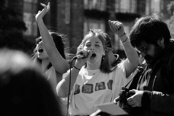 Auf dem schwarz-weiß-Bild wird eine Szene einer Demonstration gezeigt. In der Mitte ist eine junge Frau, die in ein Mikrofon ruft. Ihre linke Faust ist in die Luft gestreckt. Neben ihr ist eine weitere Frau, die ihre Hand in die Luft streckt. Am rechten Bildrand steht ein Fotograf, der auf seine Kamera guckt.