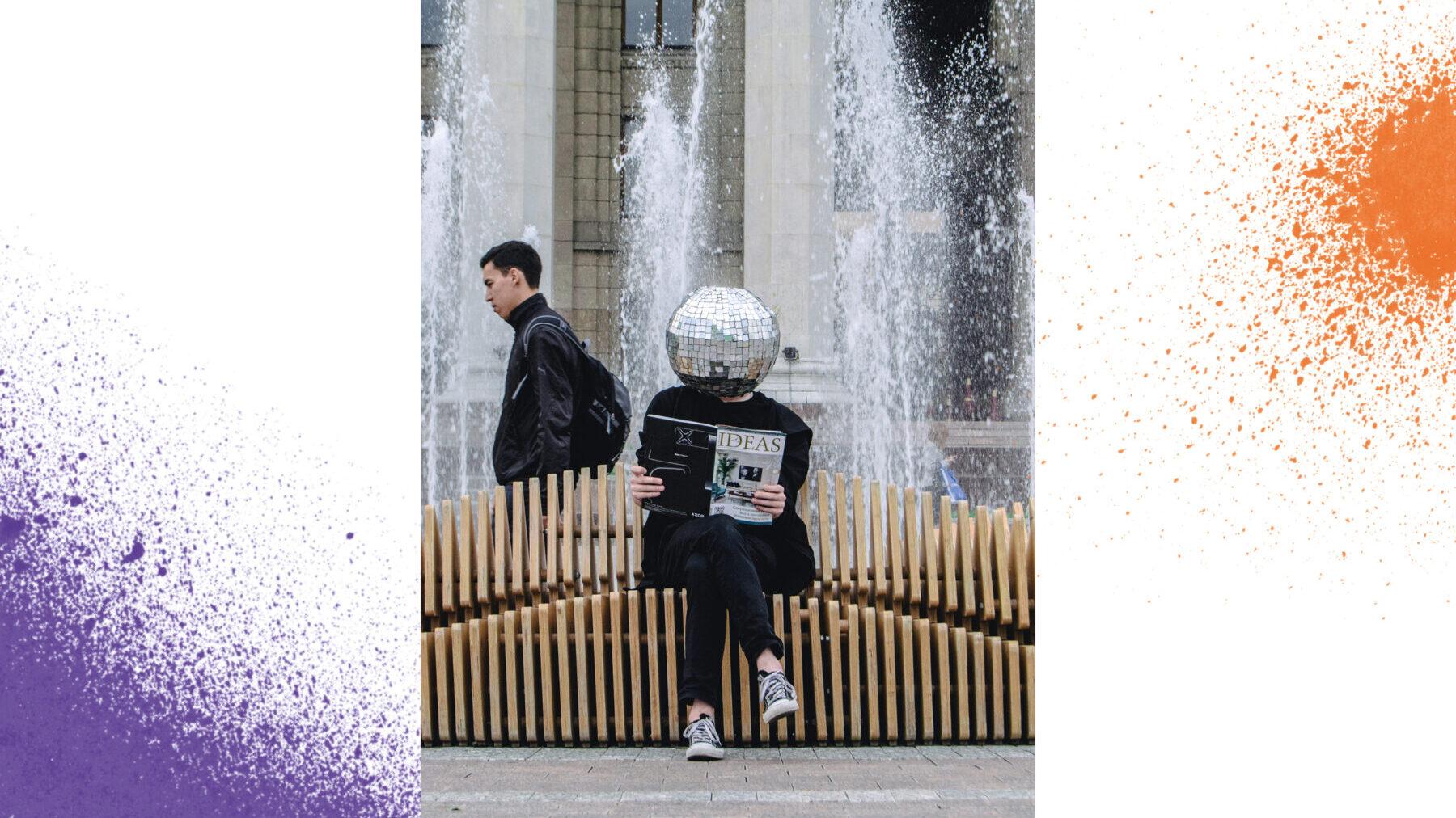 """Eine Person mit Diskokugel anstelle eines Kopfes sitzt auf einer hölzernen Bank vor einem städtischen Springbrunnen. Sie liest ein Magazin mit dem Titel """"Ideas""""."""