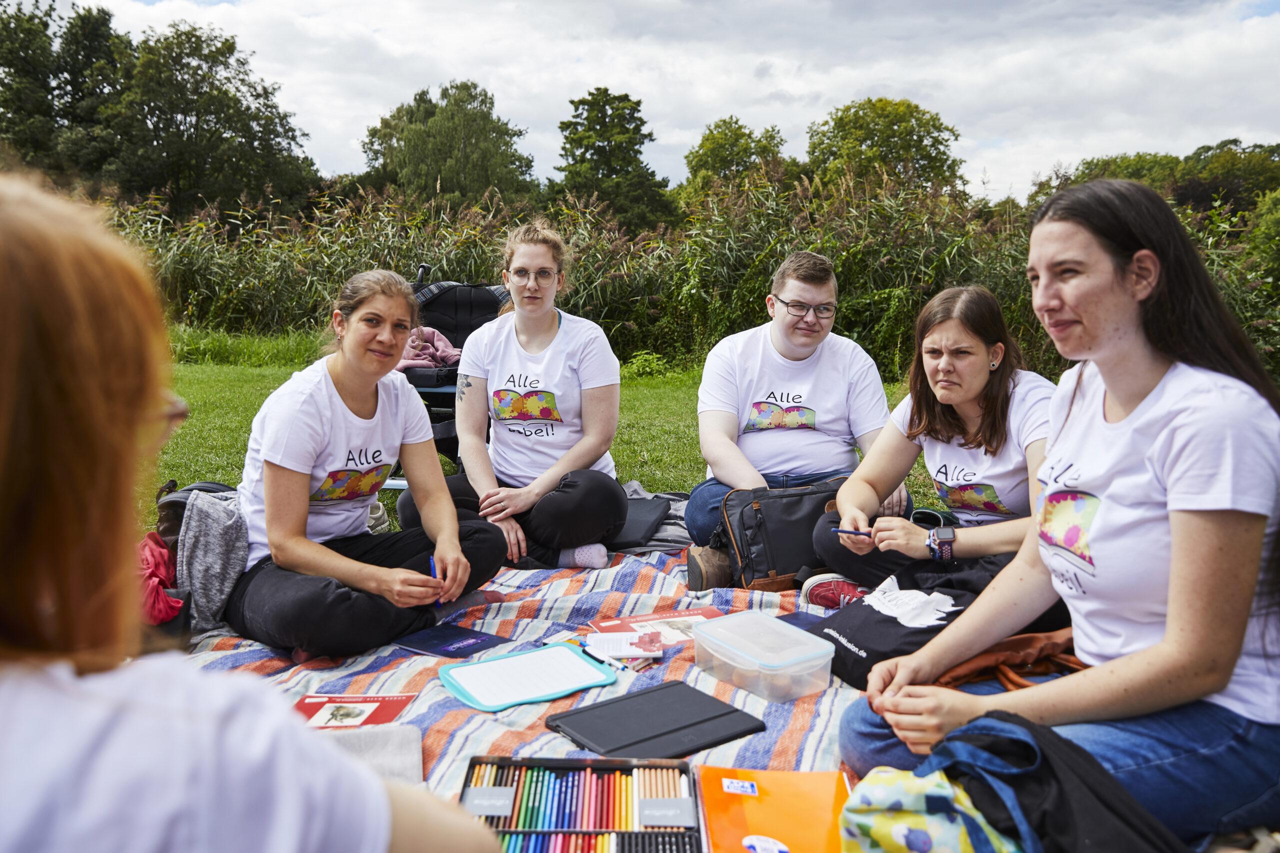 """Das Bild zeigt fünf junge Menschen mit und ohne Behinderung, die auf einer Decke auf einer Wiese sitzen. Alle tragen T-Shirts mit der Aufschrift """"Alle dabei"""" © Servicestelle Jugendbeteiligung / Aktion Mensch I Anna Spindelndreier"""