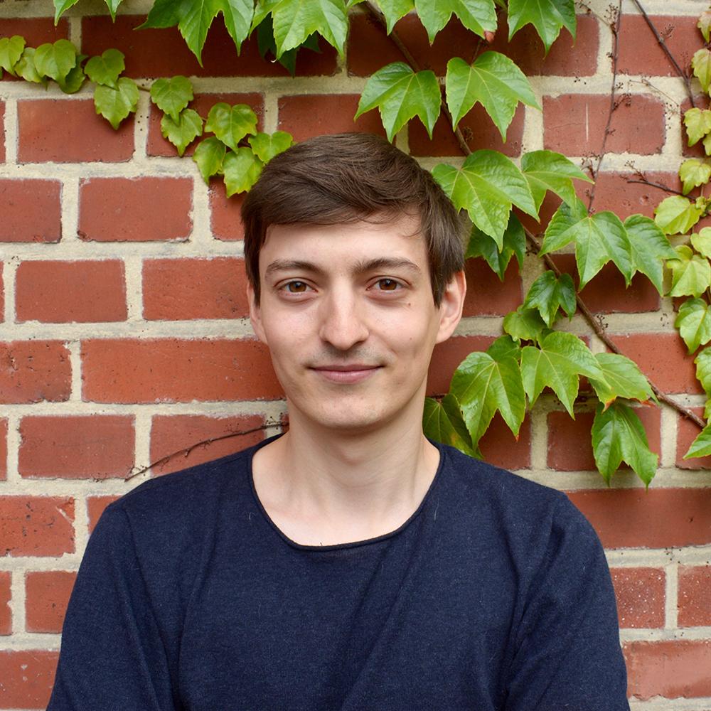 Das Bild zeigt Fabian. Er steht vor einer mit Efeu bewachsenen Backsteinwand und lacht in die Kamera. © Servicestelle Jugendbeteiligung e.V., 2019