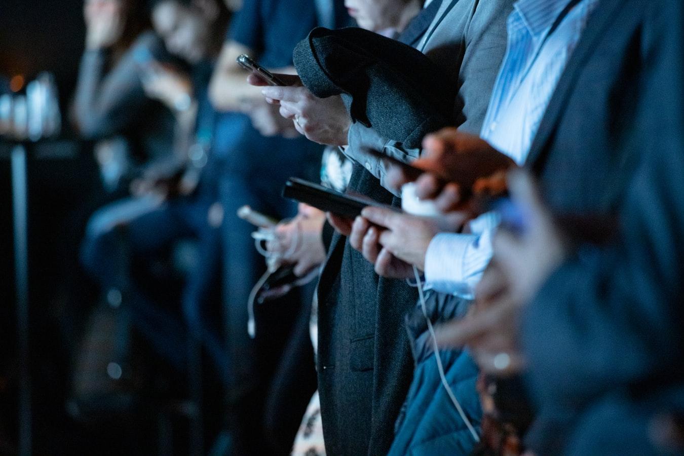 Es sind mehrere Menschen mit Smartphone in der Hand zu sehen.