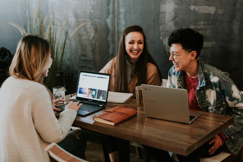 Es sind drei junge Personen, die vor ihrem Laptop sitzen zu erkennen. Alle lachen.