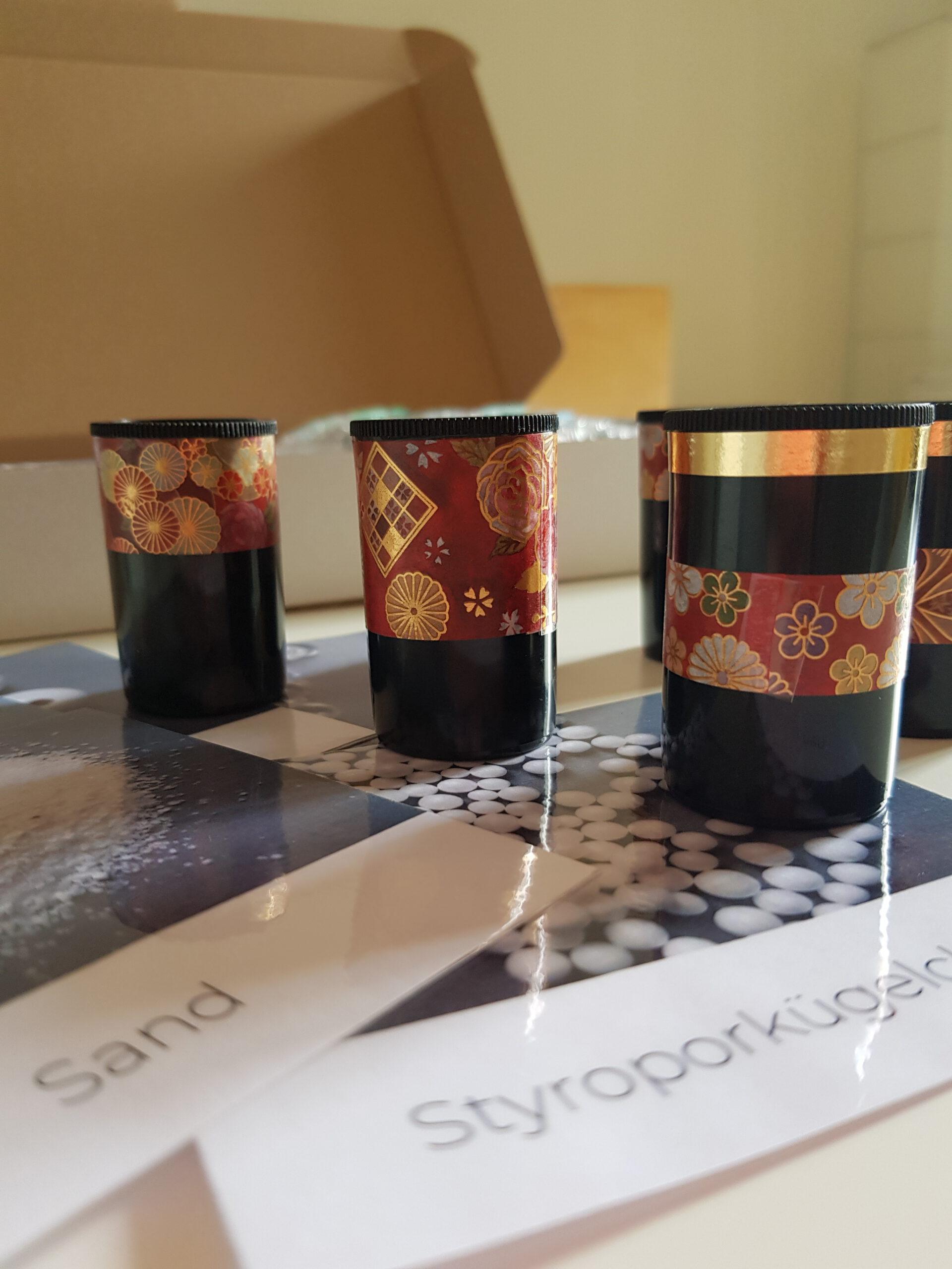 Das Bild zeigt Teile des Geräusche-Memorys. Zu sehen sind schwarze verzierte Filmdosen. Darunter liegen laminierte Spielkarten. © Servicestelle Jugendbeteiligung e.V., 2021