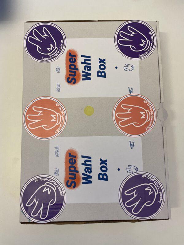 Ein Bild der bunten SuperWahlBox mit coolen Stickern drauf © SJB, 2021